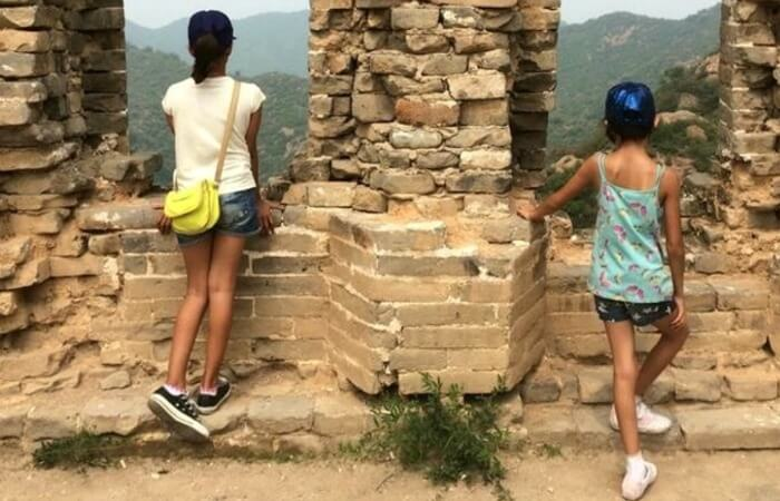 China family holidays - two girls look out from the Great Wall of China