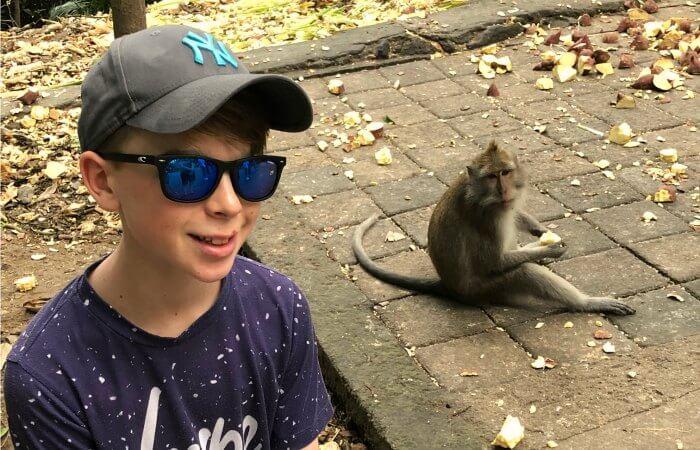 Child posing with monkey on