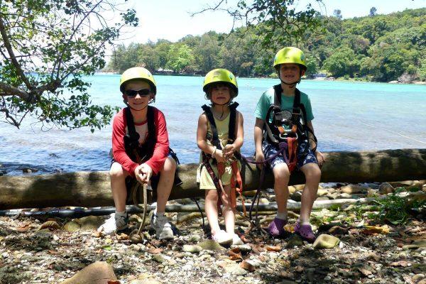 Borneo with kids - three children preparing to go on zip-wire between islands in Borneo