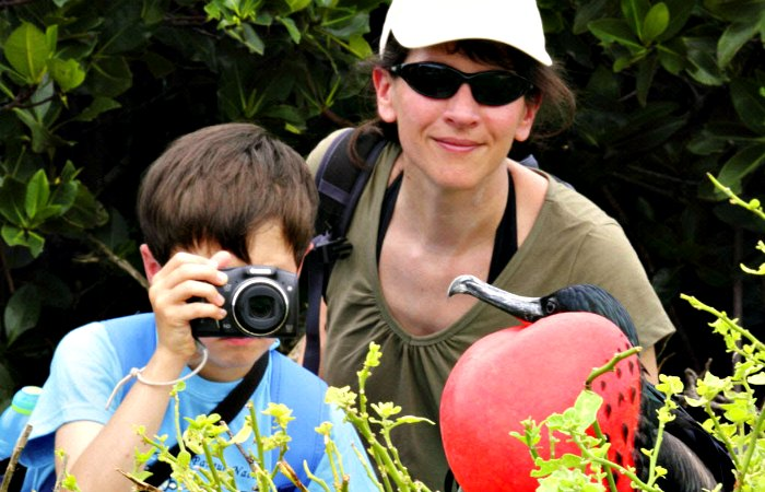 Child taking photo of Frigate bird on a Galapagos family trip