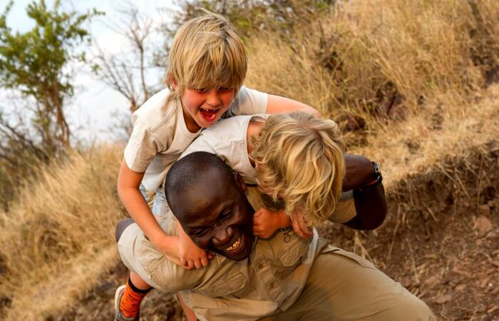 Solo and single parent holidays in Tanzania - kids playing with the guide