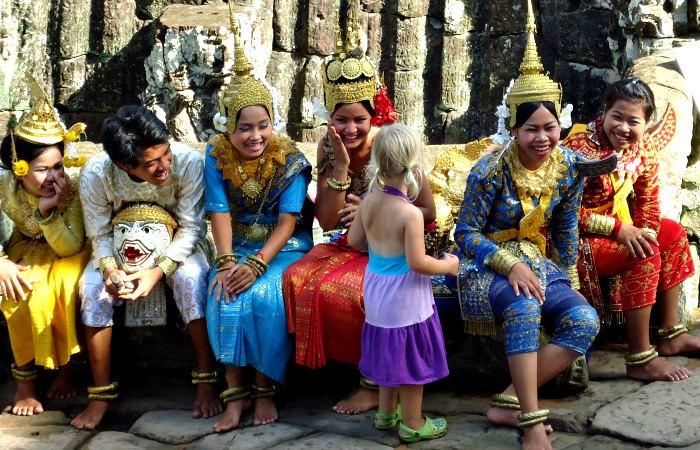 Cambodia with kids holiday, young girl meets dancers at Angkor Wat