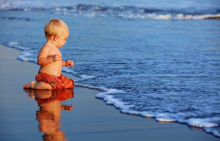 Toddler sitting on Bali beach - toddler friendly holidays in Bali
