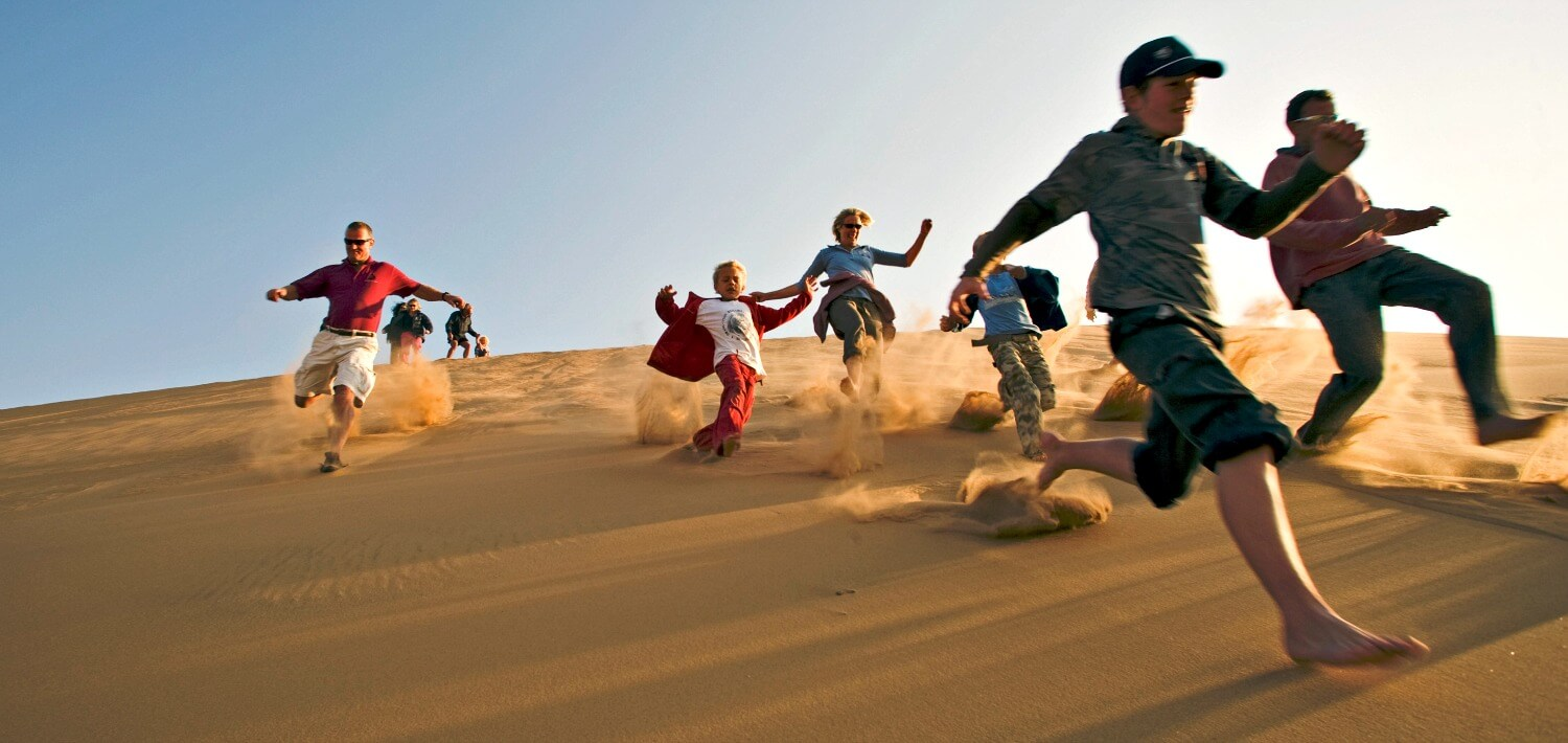 Family on holiday running down sand dunes together