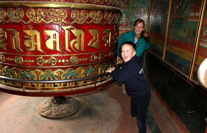 Children enjoying giant prayer wheel in Nepal