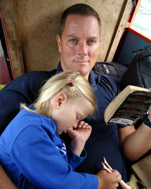 Child asleep on dad - kids holidays abroad blog