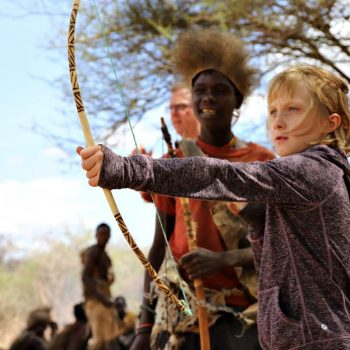 Kids learning to use a traditional bow and arrow on a Tanzania with kids holiday