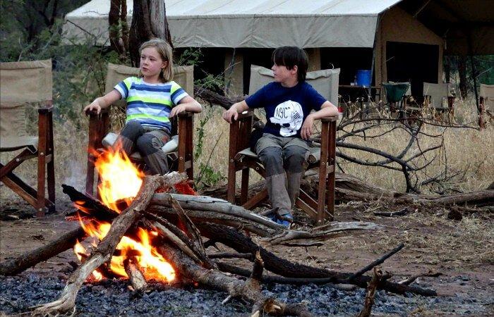 Kids sitting around a campfire in the Serengeti