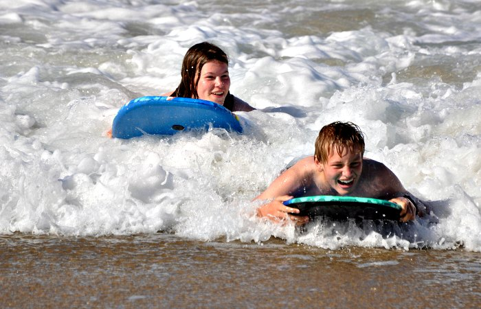 Teenagers body boarding on South Africa with children family holiday