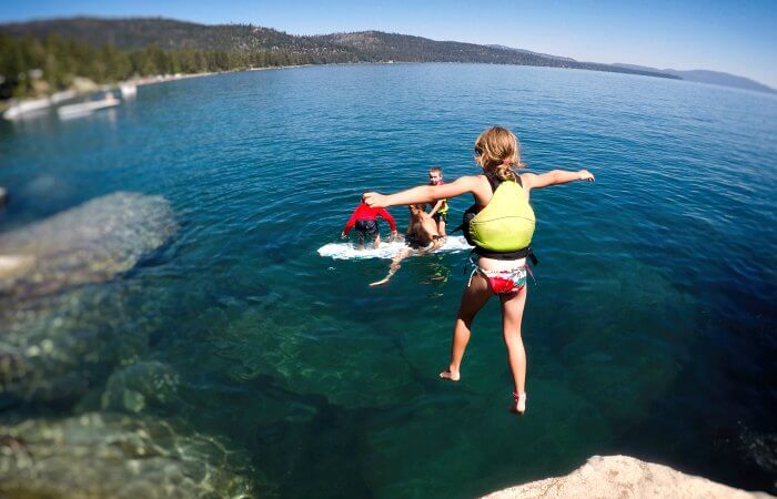 Swimming in Lake Tahoe with child jumping in, on a US family road trip
