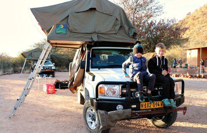 Kids sitting on car bonnet - Namibia family road trip
