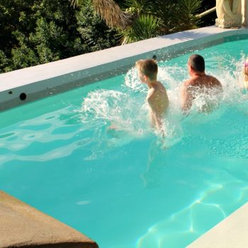Family jumping into pool on family summer holiday